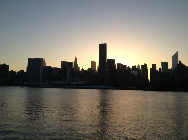 View of the NYC skyline as the sun hides behind the buildings.